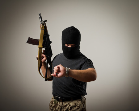 Terrorist with gun looking at his wristwatch. Time concept. photo