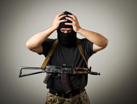 tiring: Frustrated man wearing balaclava with a gun. Headache concept.