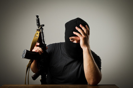 Frustrated man wearing balaclava with a gun. Headache concept. photo
