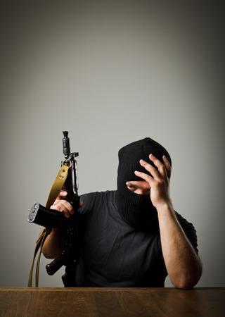 Frustrated man wearing balaclava with a gun  Headache concept  photo