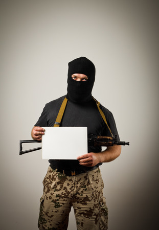 obscurity: Man in mask with gun is holding white paper