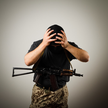 tiring: Frustrated man wearing balaclava with a gun  Headache concept  Stock Photo