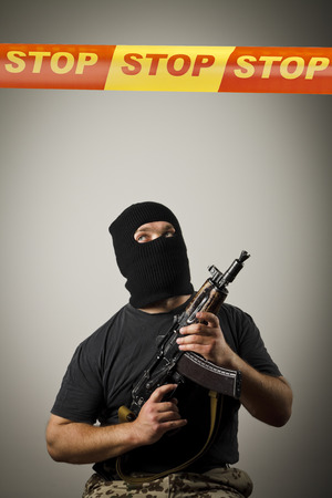 Man in mask with gun and STOP line over his head. Restricted area concept. photo