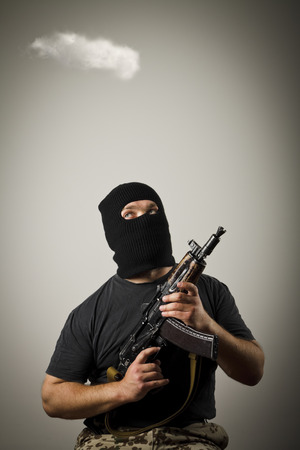 Man in mask with gun and white cloud. Imagination concept. photo