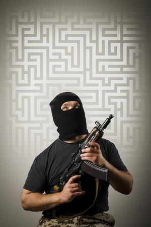 crime solving: Man in mask with gun solving maze. Maze concept.