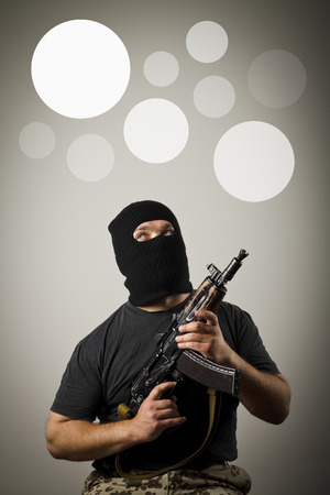 Man in mask with gun having an idea with gray bubbles over his head. photo