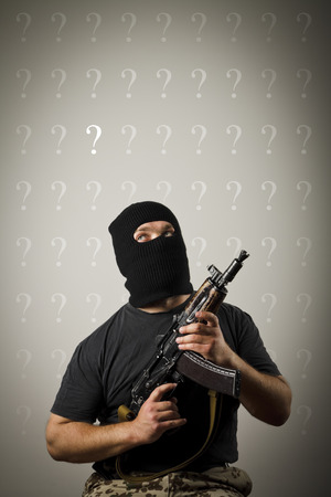 Man in mask with gun and question marks above head. photo