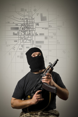 annexation: Man in mask with gun and city map. Invasion concept. Stock Photo