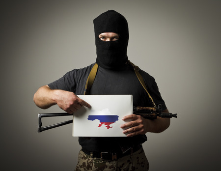obscurity: Man in mask with gun is holding white paper with a map of Ukraine. Stock Photo