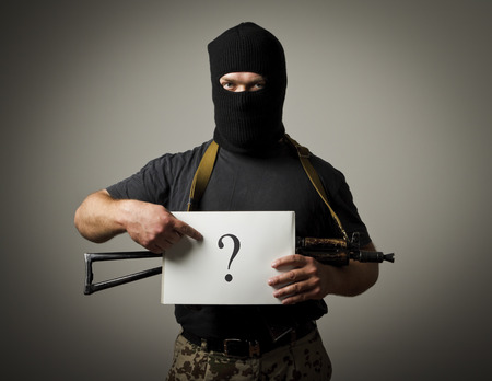Man with gun holding white paper with question-mark. Man having no answers to a question. Imagens