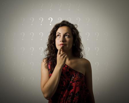esitazione: Ragazza piena di dubbi e esitazioni. Ragazza e molti punti interrogativi sopra la testa. Giovane donna che fa qualcosa. Archivio Fotografico