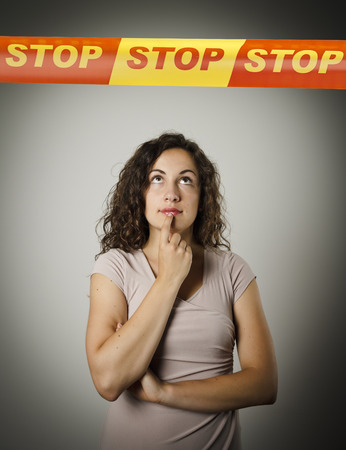 touchline: Girl and STOP line over her head. Restricted area concept. Young woman doing something. Stock Photo