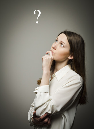 Girl in white full of doubts and hesitation. Girl and question mark above her head. Girl is thinking. Stock Photo