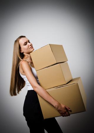 Vrouw met een stapel van verpakte pakketten. Vrouw doet iets. Carton. Stockfoto