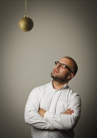 waiting glance: Man in white and Christmas ball which is above his head. Waiting of Christmas and New Year.