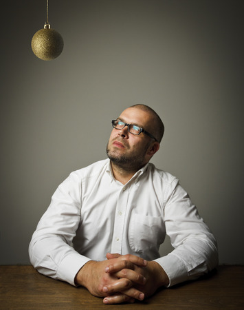 Man in white and Christmas ball which is above his head. Waiting of Christmas and New Year.