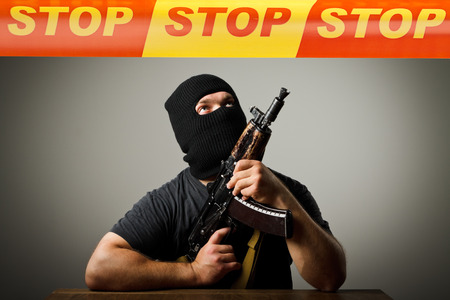 looter: Man in mask with gun and STOP line over his head. Restricted area concept. Stock Photo