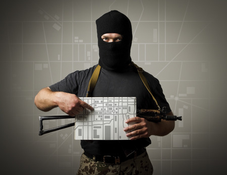 Man in mask with gun is holding a city map. Evacuation concept.