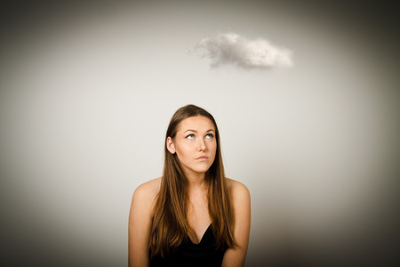 mystique: Girl and white cloud. Imagination concept. Young woman doing something. Stock Photo