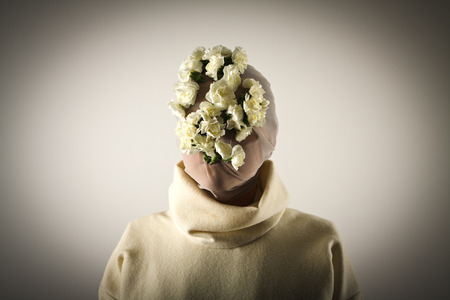 Young girl in white wearing a floral mask. photo