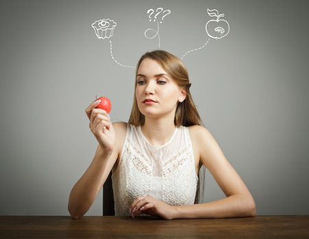 hesitation: Girl in white is sitting and holding an apple. Doubt or fast food concept.