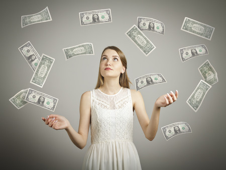 jubilate: Girl in white and falling dollar banknotes. Currency and lottery concept. Stock Photo