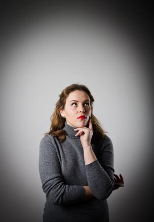 esitazione: La ragazza in grigio � pieno di dubbi e esitazioni. Ragazza che risolvere un problema.