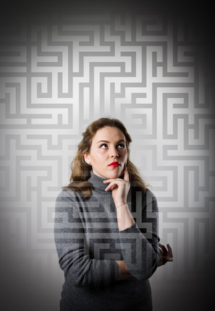 hesitation: Girl in grey full of doubts and hesitation. Girl looking for the solution. Maze concept.