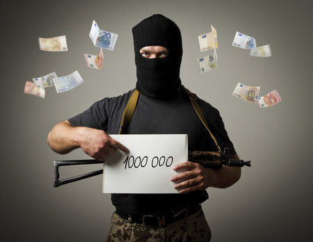 ransom: Man in mask with gun is holding white paper with a sign. Ransom, tribute and racketeering concept.