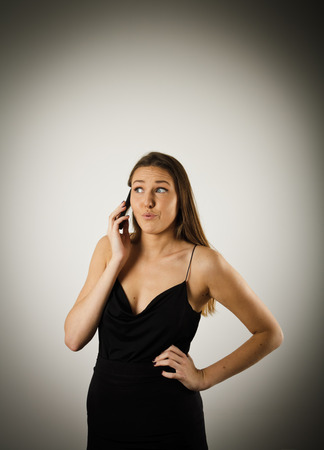 slander: Gossip. Beautiful woman talking on the phone. Young woman is doing something.