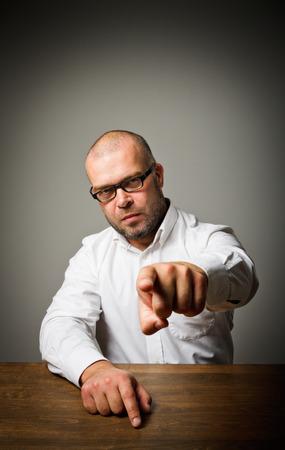 jefe enojado: Acusaci�n. Hombre en una larga mesa de madera est� indicando algo.