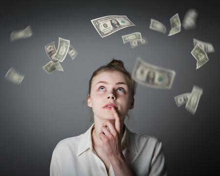 dollaro: Ragazza in bianco e cadendo le banconote in dollari. Valuta e il concetto della lotteria. Giovane donna sottile.