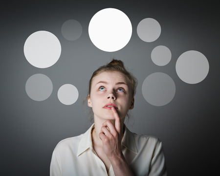 Girl in white having an idea with gray bubbles over her head. Young slim woman. Stock Photo
