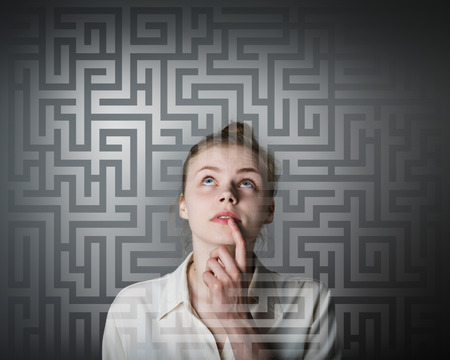puzzle background: Young woman looking for the solution. Young slim woman. Stock Photo