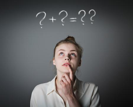 esitazione: Ragazza in bianco pieno di dubbi e esitazioni. Ragazza e il punto interrogativo sopra la sua testa. Giovane donna sottile.