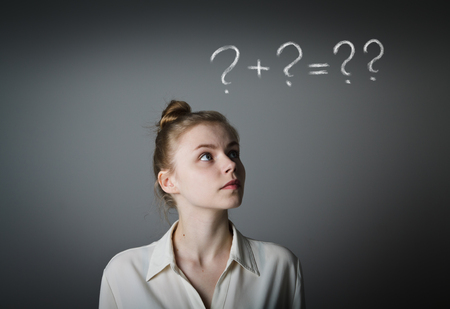 hesitation: Girl in white full of doubts and hesitation. Girl and question marks above her head. Young slim woman. Stock Photo
