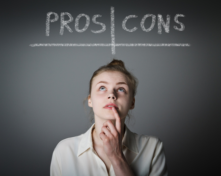 cons: Girl in white is thinking. Pros and cons concept. Young slim woman.