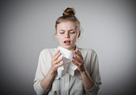 rheum: Young slim woman is sneezing.