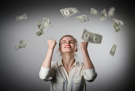 lottery win: Rejoicing. Young slim woman and falling dollar banknotes. Success, currency and lottery concept.