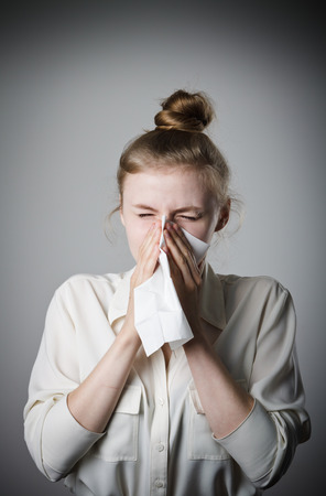 Young slim woman is sneezing.