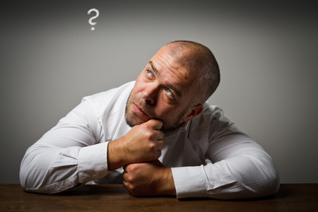 hesitation: Man in white and question mark above head. Man is solving a problem. Stock Photo
