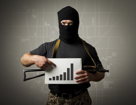 Man in mask with gun is holding a diagram. Terrorism concept. 版權商用圖片