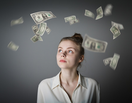 exult: Girl in white and falling dollar banknotes. Currency and lottery concept. Young slim woman.