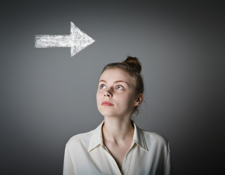 hesitation: Young slim woman is looking at arrow. Girl in white full of doubts and hesitation. Stock Photo