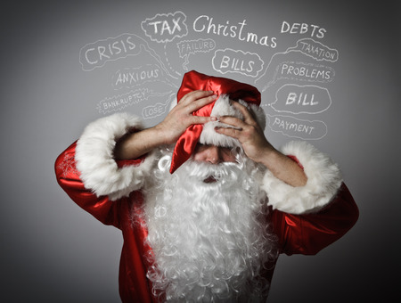 chagrin: Frustrated Santa Claus. Christmas, taxes, debts and other problems. Santa Claus suffering from headache. Stock Photo