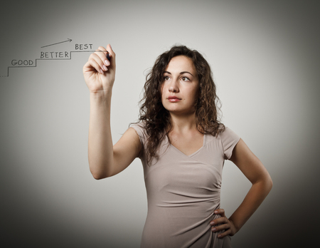 good better best: Young woman is writing the words GOOD - BETTER - BEST. Young woman is doing something. Stock Photo