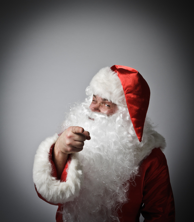 Santa Claus is showing at somebody. Imagens