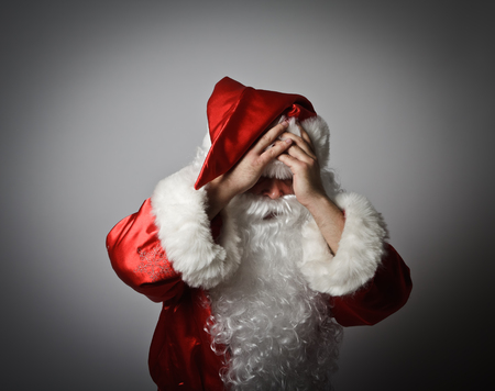 chagrin: Frustrated Santa Claus. Santa Claus suffering from headache. Stock Photo