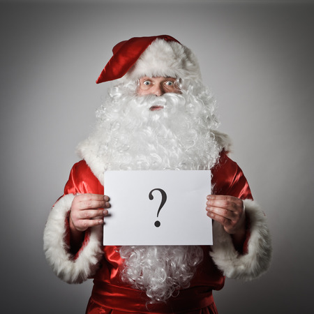 obscurity: Santa Claus is holding white paper with question-mark. Stock Photo