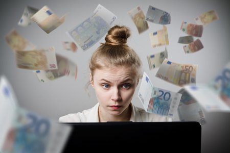 earns: Young slim woman using a laptop to browse the net. Woman earns money on the internet. Stock Photo